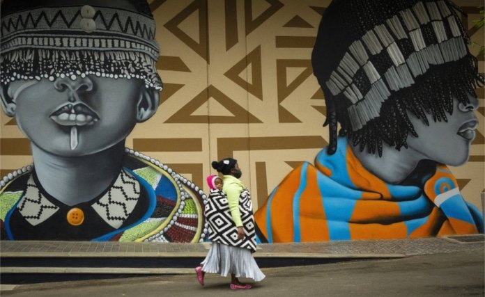 A mother carries her child on her back as she walks past murals featuring graphic prints and two elaborately dressed figures.