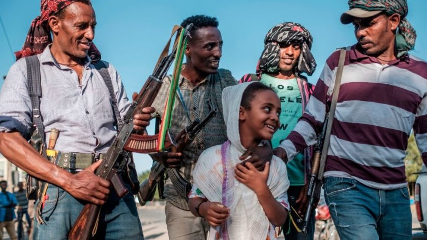 Ethiopian Amhara fighters in Mai Kadra, Tigray region, posing for a photo with a young girl - 21 November 2020