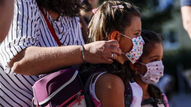 Children have their masks adjusted on the way to school in Germany