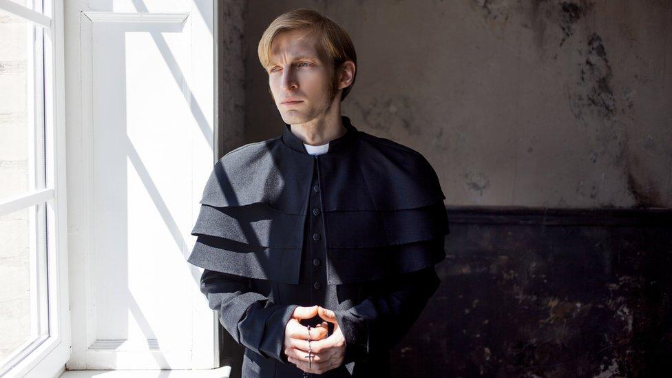Un joven sacerdote católico mira a través de una ventana