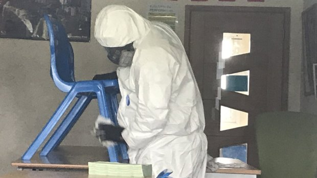 Person in full PPE cleaning a school chair
