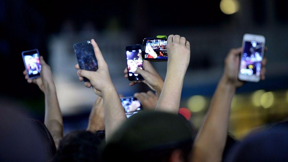 Manos sosteniendo teléfonos celulares