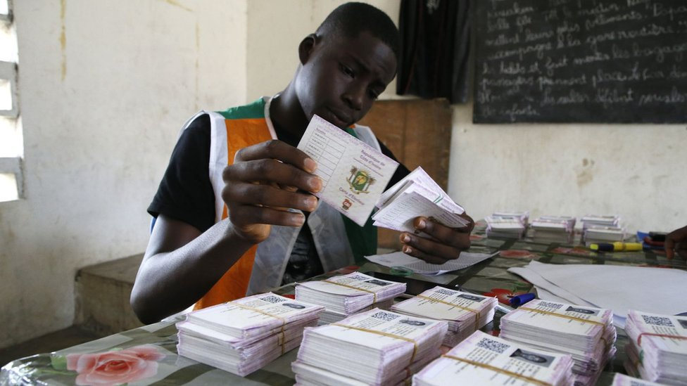 An Ivory Coast Electoral Commission official holds voting cards during distribution of voting cards ahead of the country