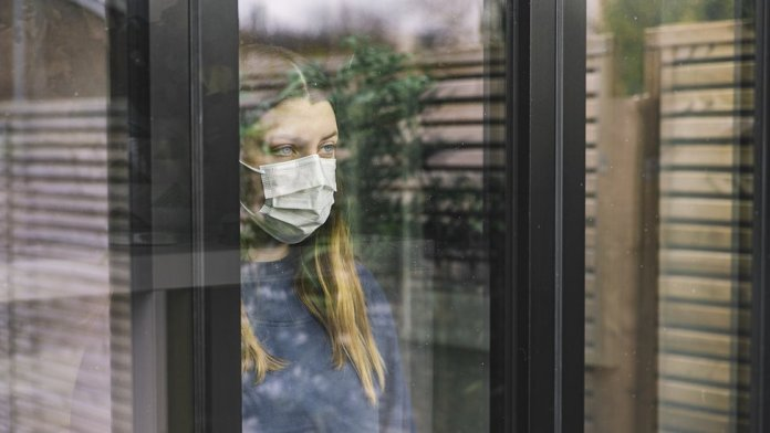 A woman with a mask behind a window.