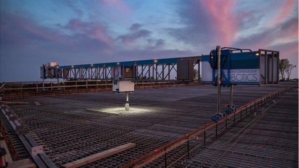 TyBot construyendo de noche en un puente.