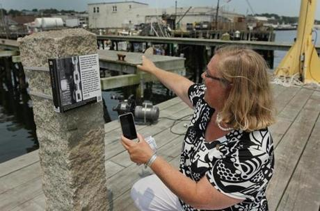 Gloucester Mayor Carolyn Kirk demonstrates how QR codes enable an interactive smartphoe tour along the city's HarborWalk.