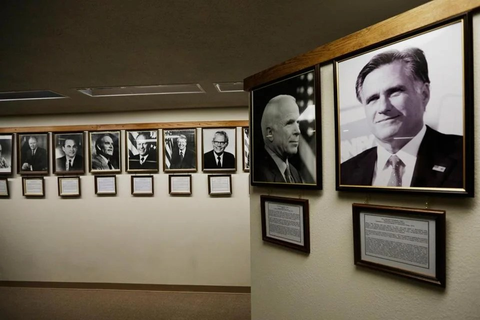 """Former Massachusetts governor Mitt Romney's portrait is the most recent addition to the """"They Also Ran Gallery,"""" above a bank lobby in Norton, Kan."""