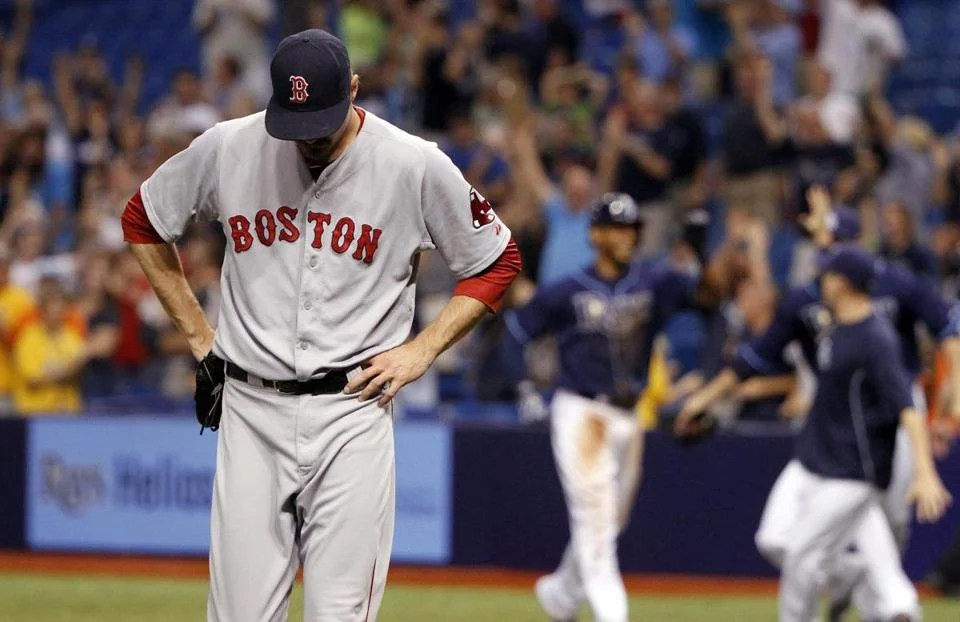 Red Sox reliever Andrew Miller walks off after his throwing error in the 15th allowed the Rays to celebrate their walkoff win. (Kim Klement/USA TODAY Sports)