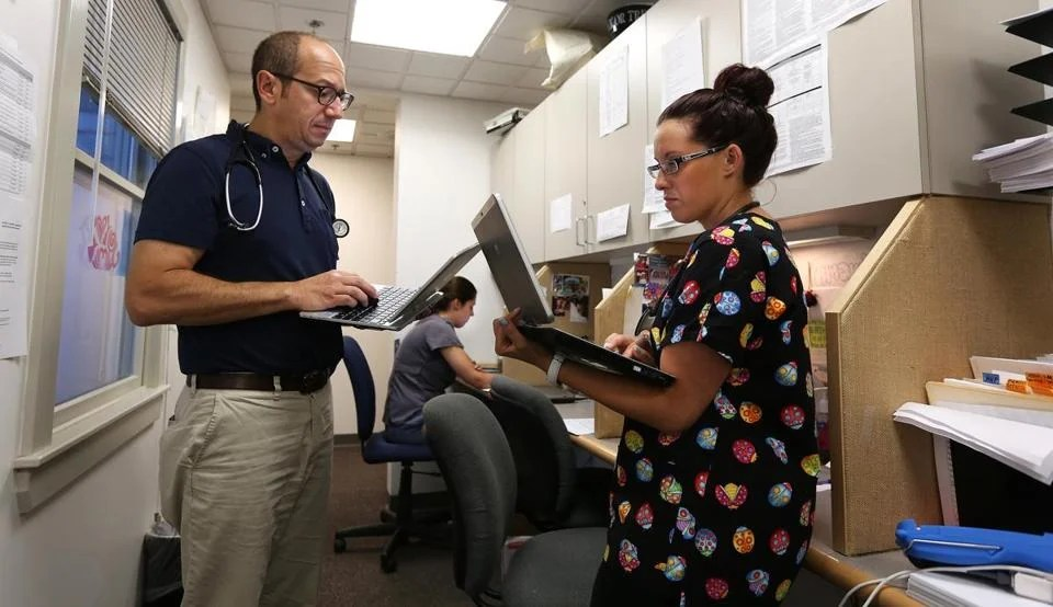 Dr. Larry Gordon and medical assistant Amanda Naimo discussed a procedure at the nurses' work station at Family Medicine Associates in Hamilton. Some doctors say their data software is confusing to use.