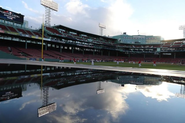 Red Sox players warm up (background) while Fenway is reflected over a water spot over the bullpen bench.
