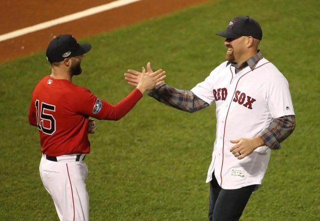 Kevin Youkilis shakes hands with Dustin Pedroia after Youkilis threw out the ceremonial pitch.
