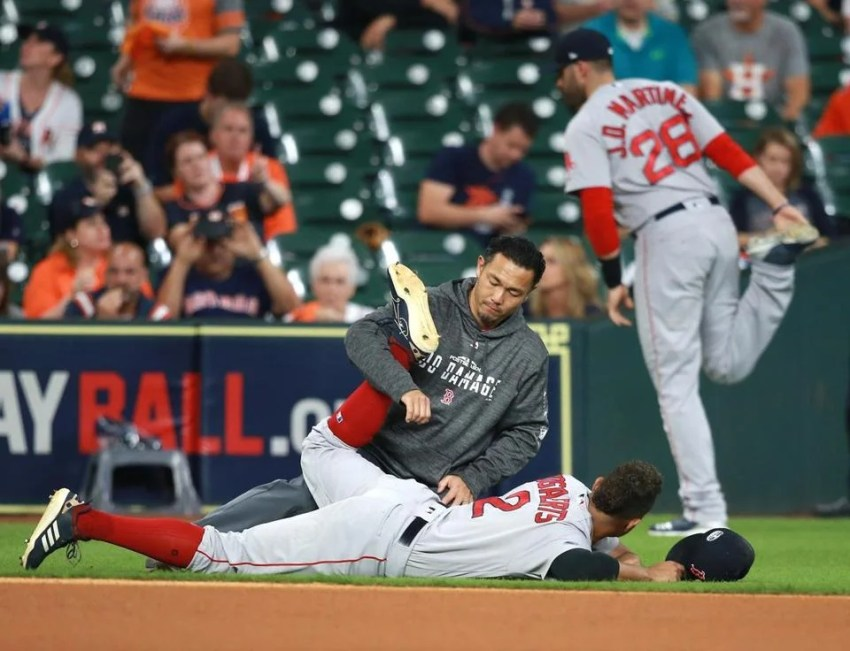 Red Sox players Xander Bogaerts (on ground) and J.D. Martinez had their own methods of stretching prior to Game 5.