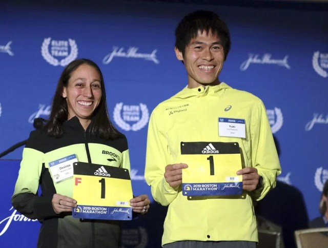 Defending champions Desiree Linden and Yuki Kawauchi show the official numbers they will be wearing in the 123rd Boston Marathon on Monday.