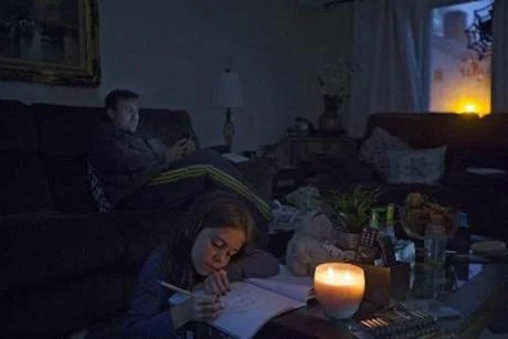 Emily Samways, 7, colored by candlelight as utility workers worked to restore power to her Wilmington Monday and her father, Mark, called the phone company about service.