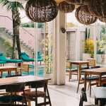 Tropical Interior Design Restaurant Tables And Chairs In Stylish Beach Club By Visualspectrum Interior Design Summer Stocksy United