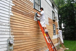 Scraping old paint from a home's exterior