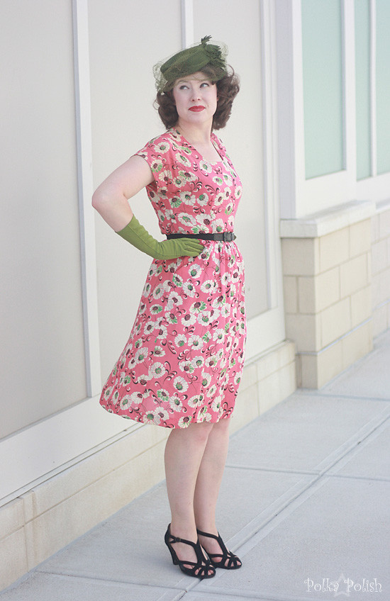 Battling wind in a 1940s salmon pink dress with green, black, and white floral print