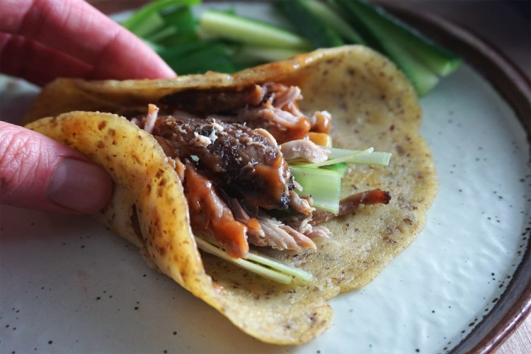 Gluten free Chinese crispy duck in pancakes with hoisin sauce, spring onions and cucumber sticks