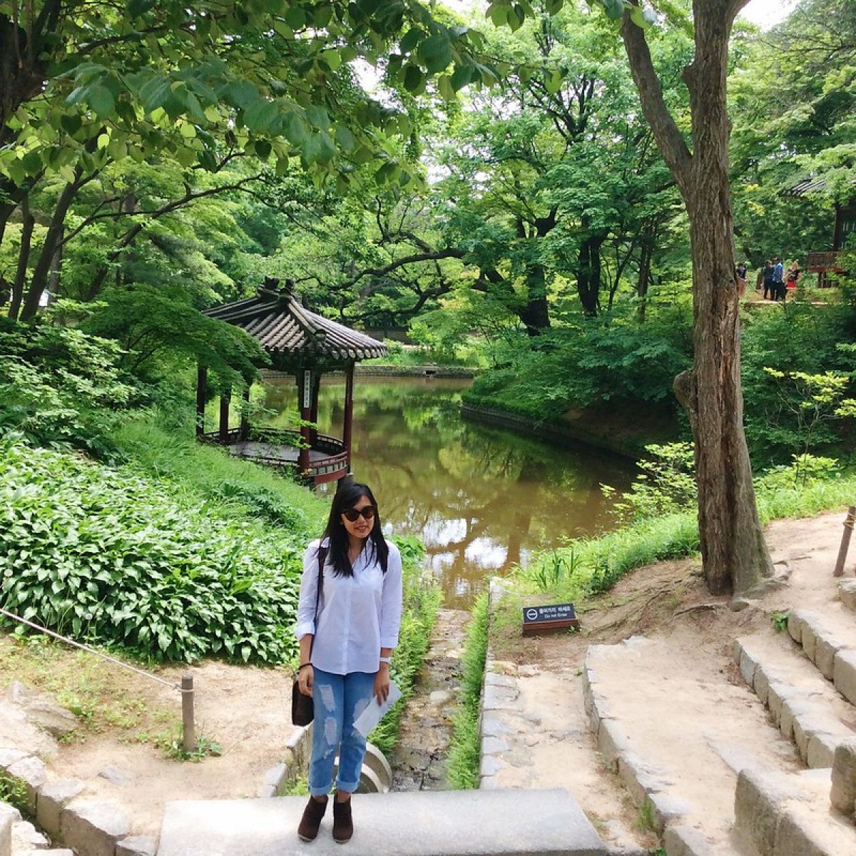 A girl in front of a gazebo in a pond in Huwon