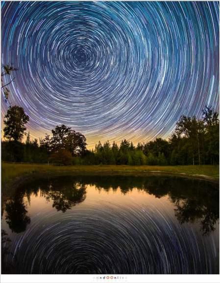 Een 'verticaal panorama' van twee foto's, beiden met een 15mm fisheye. De voorgrond is 10 minuten belicht met ISO800, de sterrensporen bestaan uit 122 opnames van 30 sec (ISO1600 - f/2,8) De reflectie is een gespiegeld kopie van de sterrensporen.
