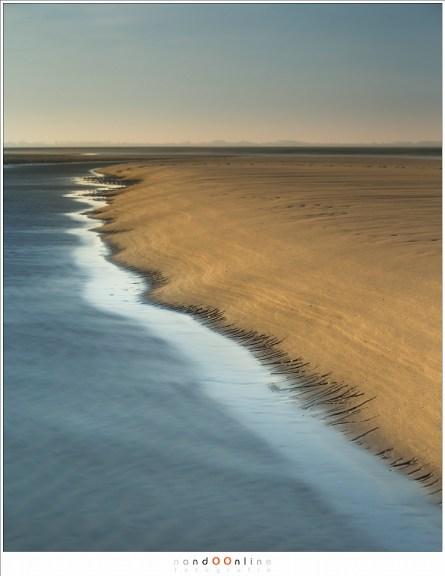 Zandbank waar het water patronen in uitgesleten heeft