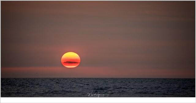 Een rode/gele zon, met een klein wolkje... Nog een paar minuten en de schemering valt in.