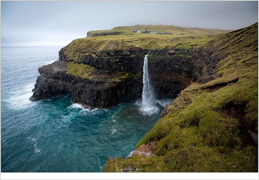 Faeröer eilanden - deel 2, Het dorp Gásadalur met de bekende waterval Mulafossur. De hoge werken rond het dorp zijn in de mist gehuld (16mm | ISO100 | f/8 | 1/15)