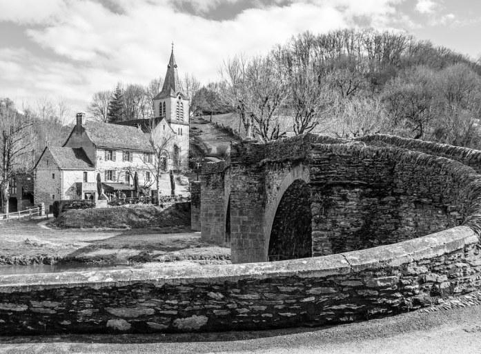 Foto en blanco y negro de la iglesia y el Pont Vieux en Belcastel