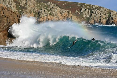 Shorebreak rainbow with bodyboarders at Porthcurno beach, Cornwall, UK