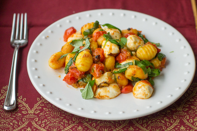 Pan-fried gnocchi with oven-roasted tomatoes, mozzarella, and heaps of fresh basil - perfect cozy date night meal!