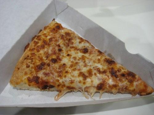 < Frozen airport pizza slice >