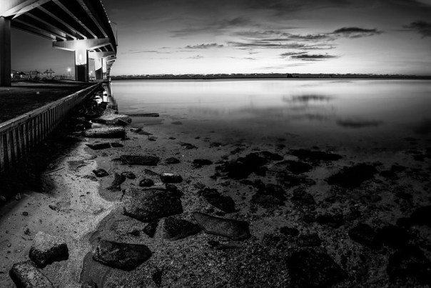 By the bridge at daybreak, alone, in black and white