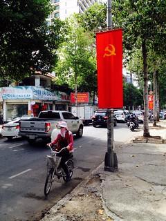 vietnamese woman cycling by a soviet flag in saigon