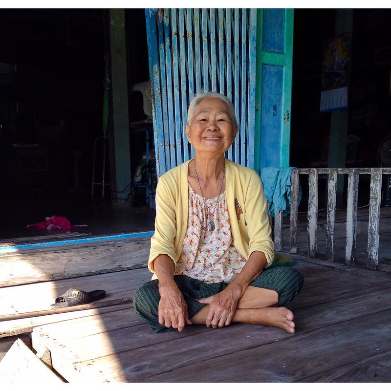 old thai woman posing for camera in squatting position in damnoen saduak floating market