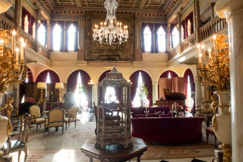 Foyer of the venetian mansion with chandeliers and a ornate silver bird cage in the center