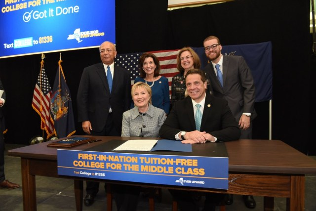 New York governor with legislatures after budget approval