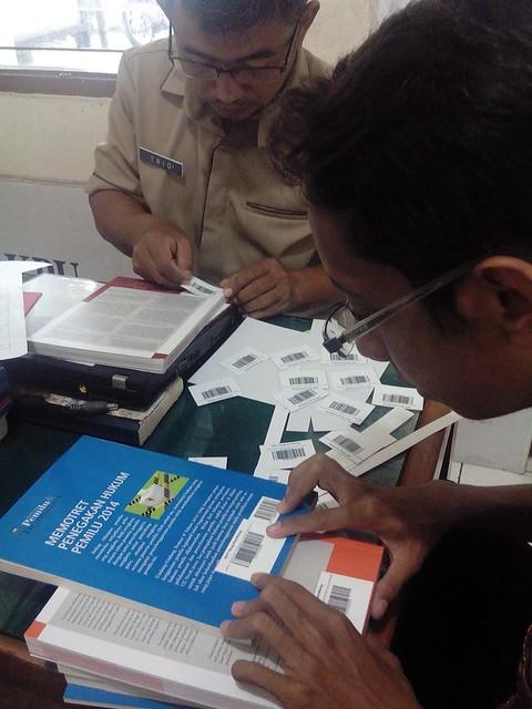 Sutriono tengah menempelkan barcode di buku koleksi RPP Reog Kendhang (8/3)
