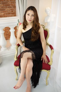 Japanese Woman Sitting In Red And Gold Chair In Black Dres