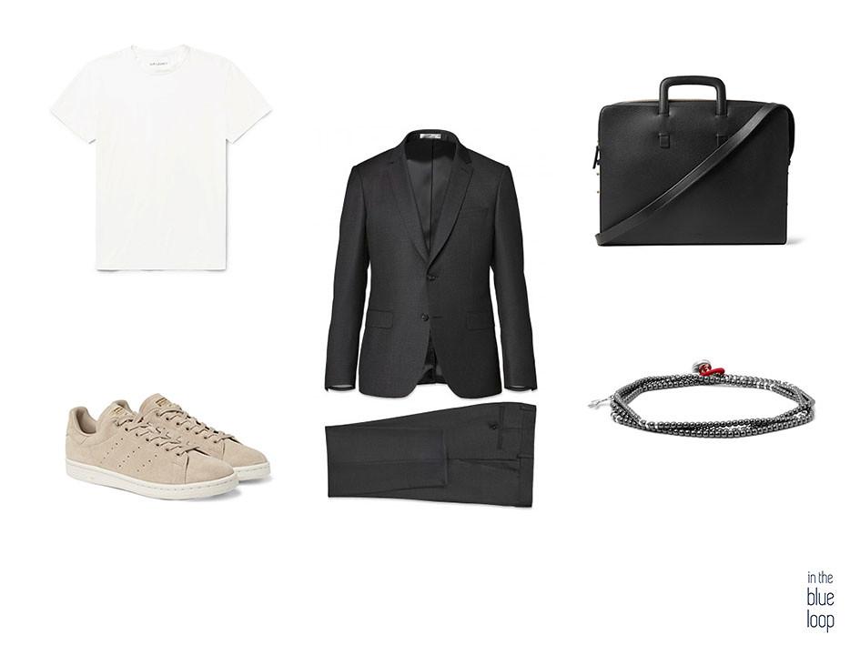 Traje hombre negro combinado con sneakers, camiseta blanca, pulsera y maletín