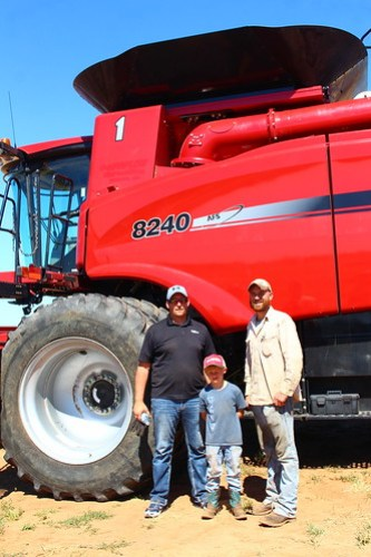 Salesman Mike, Brady and John, posing by the new combine.