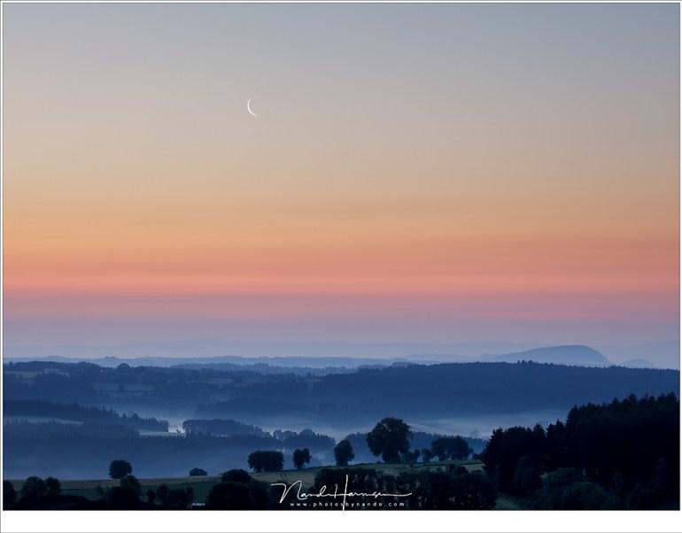 Ochtendschemering, met een smalle Maansikkel boven het heuvellandschap.