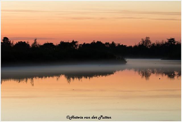 De mist die opkomt boven het water terwijl de lucht kleurt.
