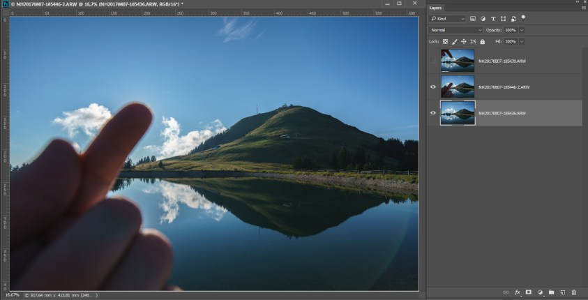 De eerste bovenliggende laag is een van de foto's met een vinger die de zon afdekt. In deze foto's zijn de flares voor de berg verdwenen, net als de flare linksboven. We kunnen in deze foto de vinger verwijderen en zo de lucht en zon weer zichtbaar maken.