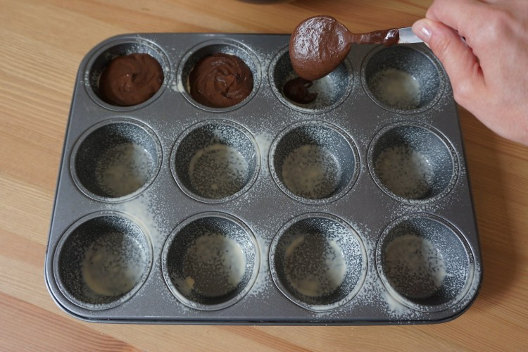 Healthy gluten free black bean brownies with S'mores on top   making process - pouring the batter in a muffin tin
