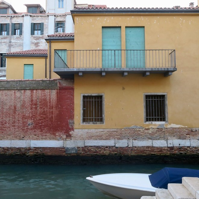 Boat and Canal on Red Wall and Yellow House with Turquoise Doors