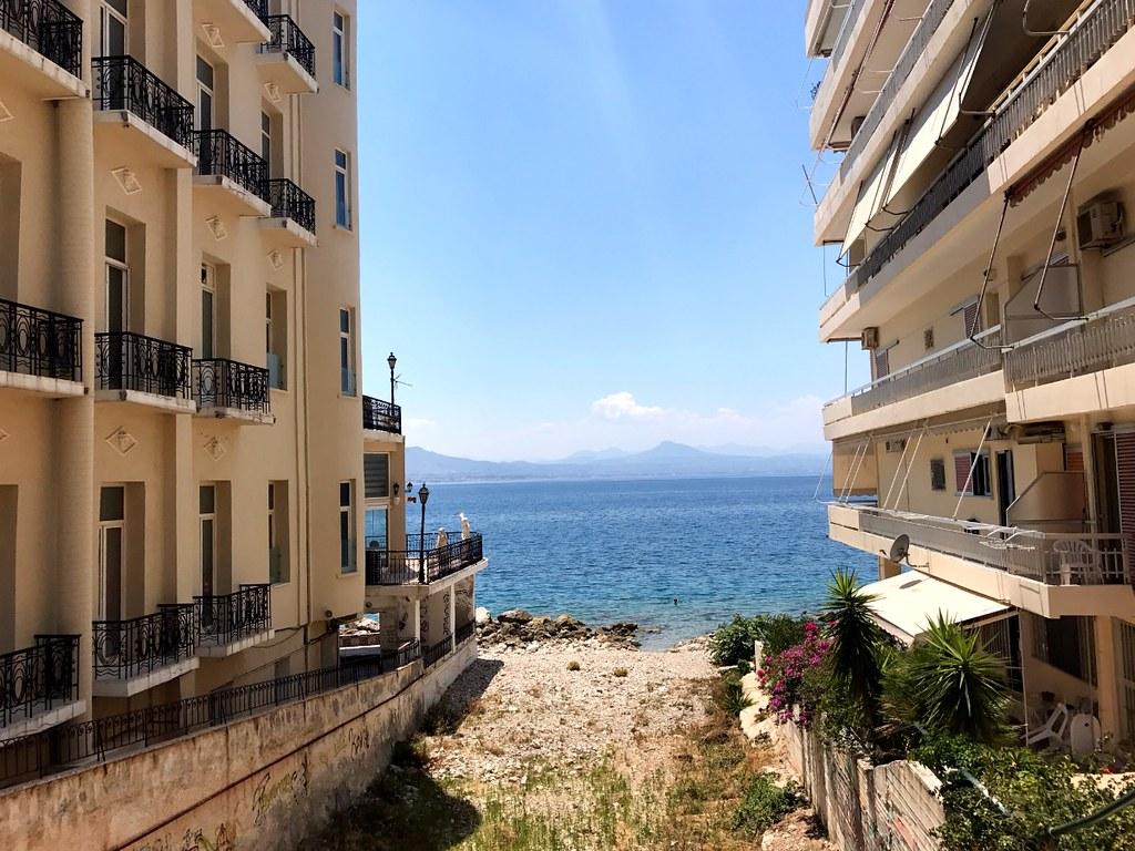 View of the Corinthian Sea between buildings in Loutraki Greece