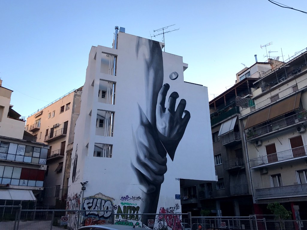 famous graffiti of hands holding each other from fall on building facade in athens