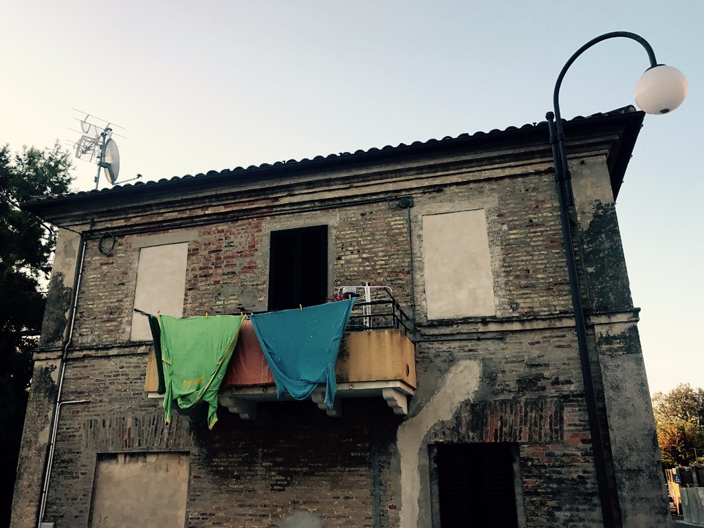 green and blue shirts hanging to dry out of a balcony of a ruined house in belvedere ostrense in italy