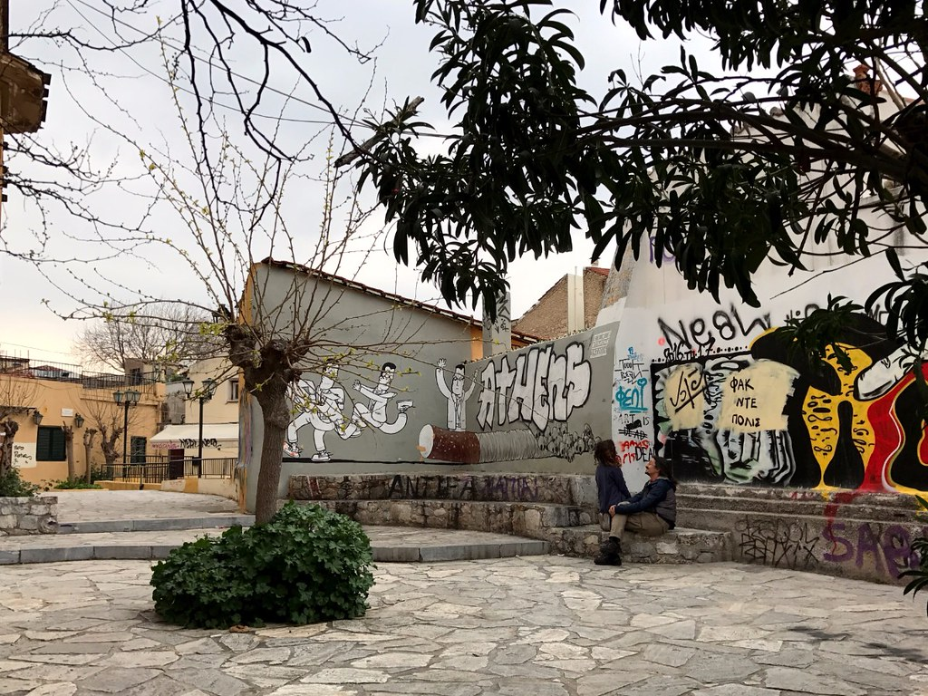 couple sitting in a little square in plaka athens