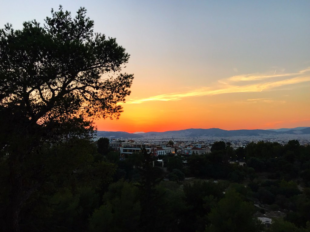 stunning sunset with fire red sky over wide view of athens from acropolis rock